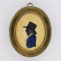 Front of silhouette, in frame, with man looking left, with a hat, wearing blue and yellow jacket.