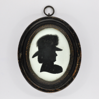 Front of Silhouette, in frame, with woman looking right and wearing a hat