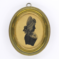Front of silhouette, in frame, with woman looking right, wearing a ribbon.