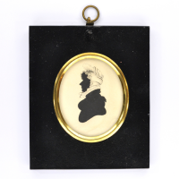 Front of silhouette, in frame, with woman looking left, wearing a bonnet.