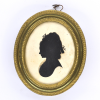 Front of silhouette, in frame, with woman looking left, wearing a ribbon.
